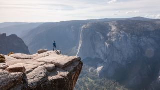 A man standing on a cliff edge overlooking Yosemite Valley