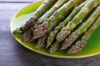 Freshly cut asparagus on a green plate.