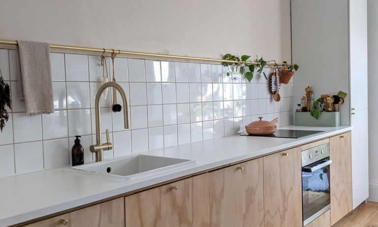 Kitchen with white countertops and wall tiles, wooden cupboards and house plants for color