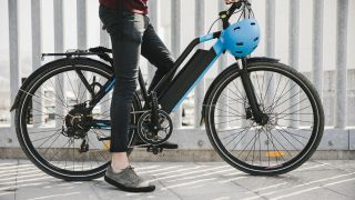 Woman in casual clothes sitting on hybrid electric bike