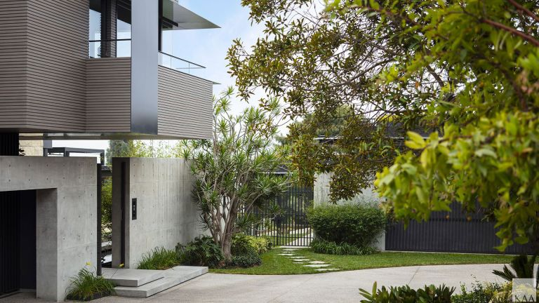 Front yard flower bed ideas in a concrete yard beside a gray modernist building.