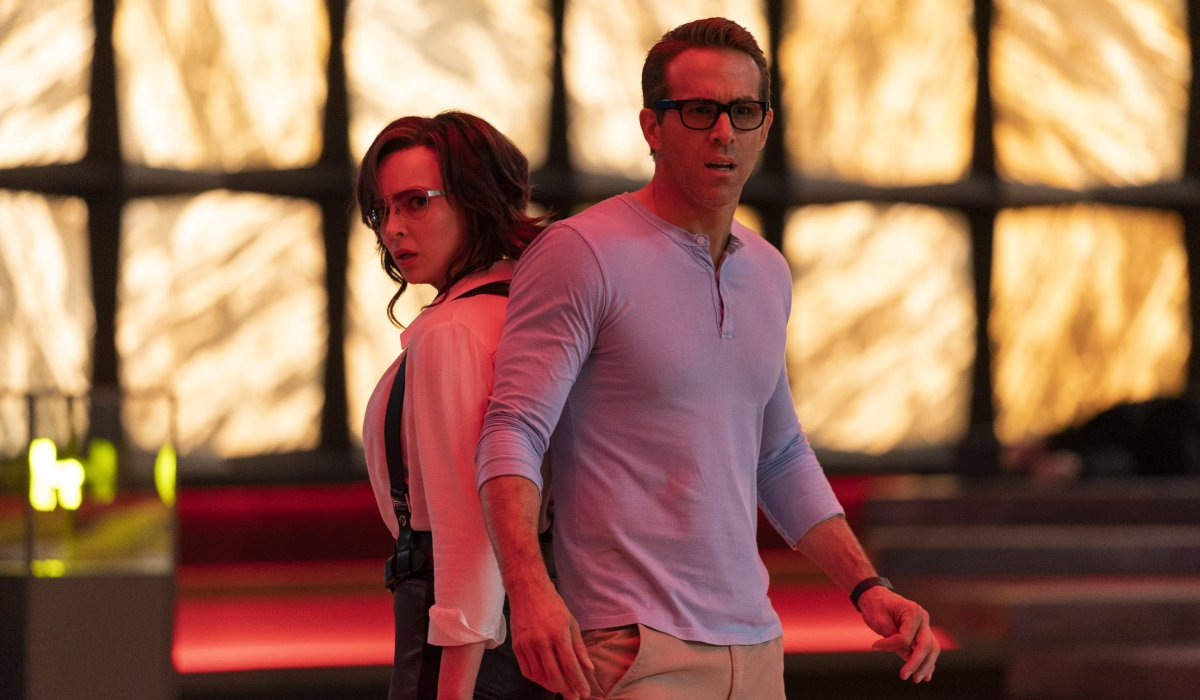 Free Guy Jodie Comer and Ryan Reynolds stand stunned, back to back