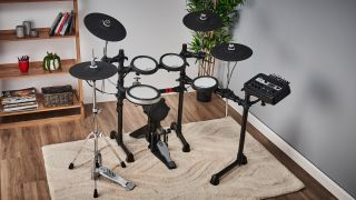 Yamaha DTX-6 electronic drum set on a cream rug, with a white wall and bookshelf in the background