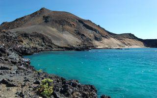 Aa lava tumbling into the sea at Sullivan Bay, Ecuador, Galapagos Islands.