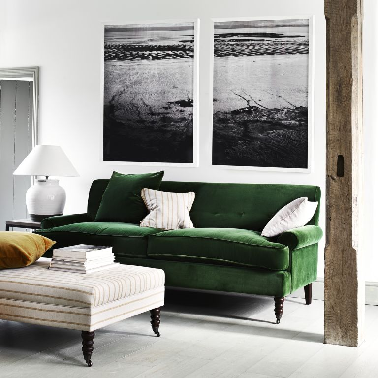 Large green velvet sofa in a monochrome living room