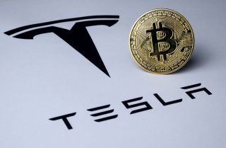 A bitcoin on top of Tesla logo