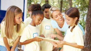 Female teacher and young students outdoors in the summer
