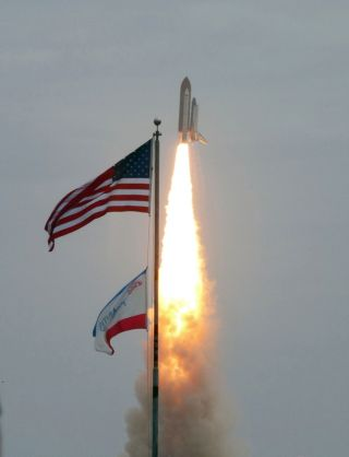 atlantis flies past flags