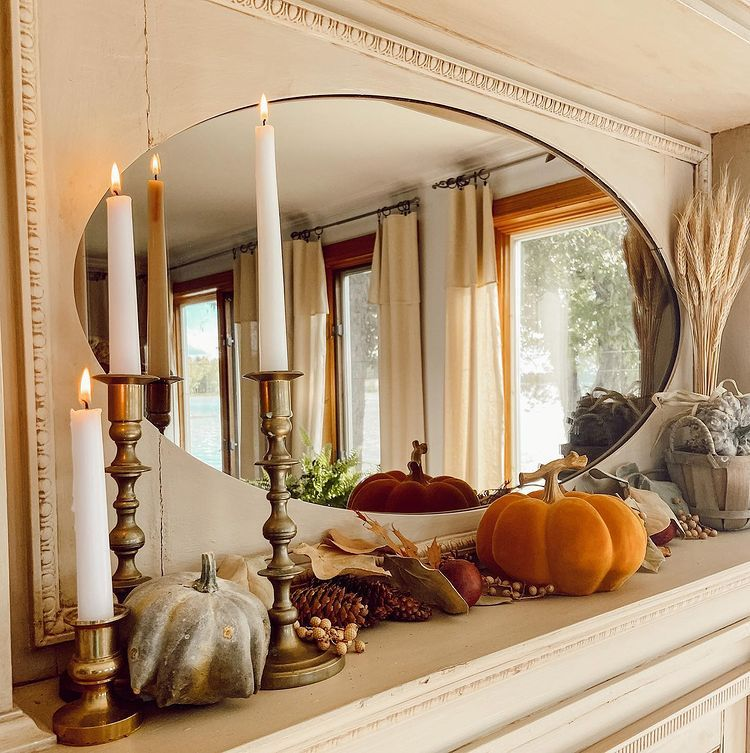 A fireplace mantel with oval mirror, pumpkins, pampas grass in a vase, candlesticks, pine cones and fall foliage