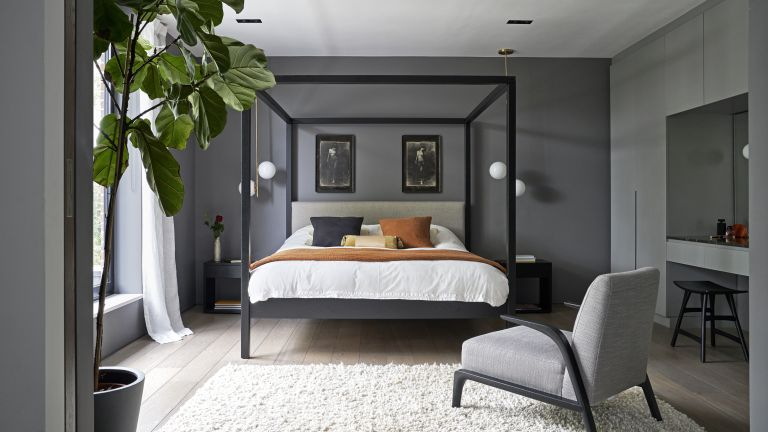 Simple bedroom ideas with dark gray walls and a black, contemporary four poster bed.