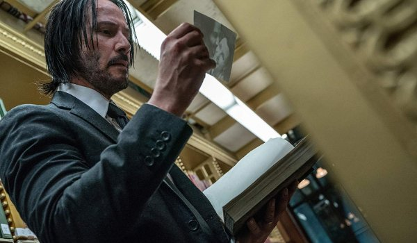 John Wick: Chapter 3 - Parabellum John looks at a photo in the library