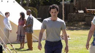 Penn Badgley walking on a field as Joe, and he'll be back for You season 3.