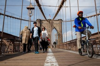 Pedestrians and cyclists cross the Brooklyn Bridge, Feb. 8, 2017, in New York City, where temperatures reached 60 degrees Fahrenheit (16 degrees Celsius).