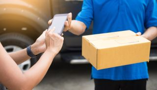Woman tapping smartphone while delivery person hands her a package.