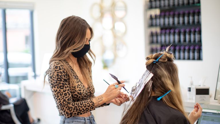 woman colouring hair at salon