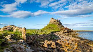 Lindisfarne castle seen from the rugged coast below it.