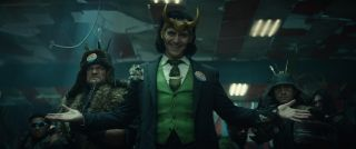 """Loki (Tom Hiddleston) stands facing the camera wearing a tattered blue suit, a green waistcoat and a green tie, a smile on his face and his arms outstretched. There is a """"LOKI"""" campaign button on his lapel. Standing behind him are various armed men."""