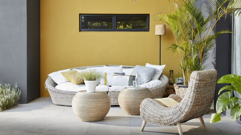 garden ideas: outdoor living area with a yellow painted wall