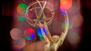 A gold Emmy statue in front of a colorful background