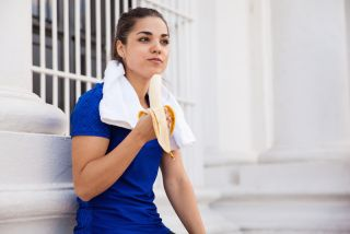 a woman eating a banana post-workout