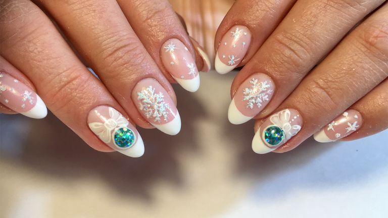 Christmas nails decorated with jewels and snowflake patterns