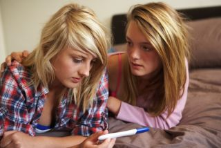 Two teen girls examine a pregnancy test result.