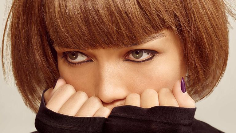 A close up of a woman with a heavy blunt fringe and a neat graphic eyeliner