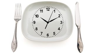 Dishware and clock. Concept restrictions in food.