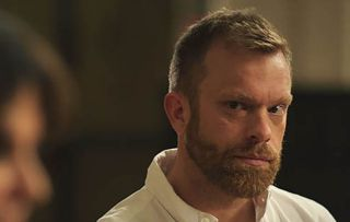 Casualty star William Beck as Dr Dylan Keogh, displaying a rare half-smile