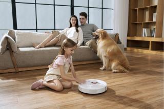 A family surrounding a Dreame D9 vacuum.