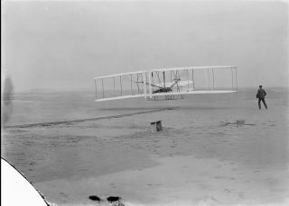 Flyer 1, controlled by Orville Wright, makes history's first powered flight at Kitty Hawk, North Carolina, on Dec. 17, 1903.Orville's brother Wilbur looks on in this photo, which was taken by John Daniels, a member of the U.S. Life-Saving Station in Kill Devil Hills, North Carolina.