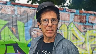 A photograph of Slim Jim Phantom stood in front of a graffiti wall