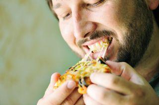 A man devours a piece of pizza.