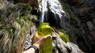 person filling up a bottle with water for hiking