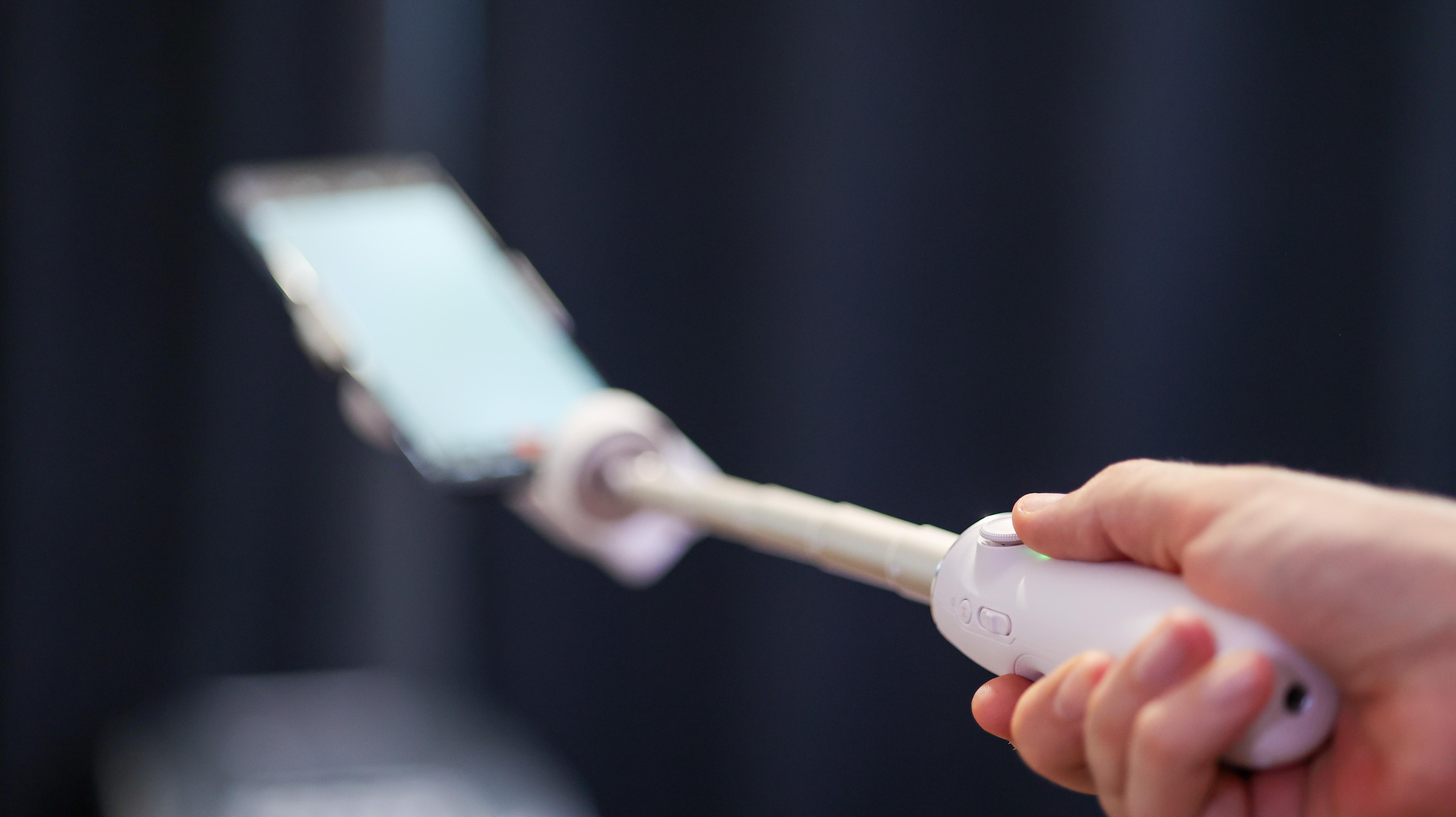 A hand holding the DJI OM 5 phone gimbal