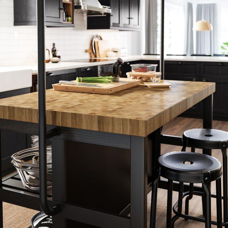 Black kitchen stools around wooden kitchen island countertops in small space