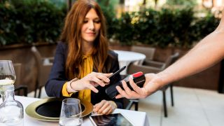 Woman pays for meal at restaurant using POS system