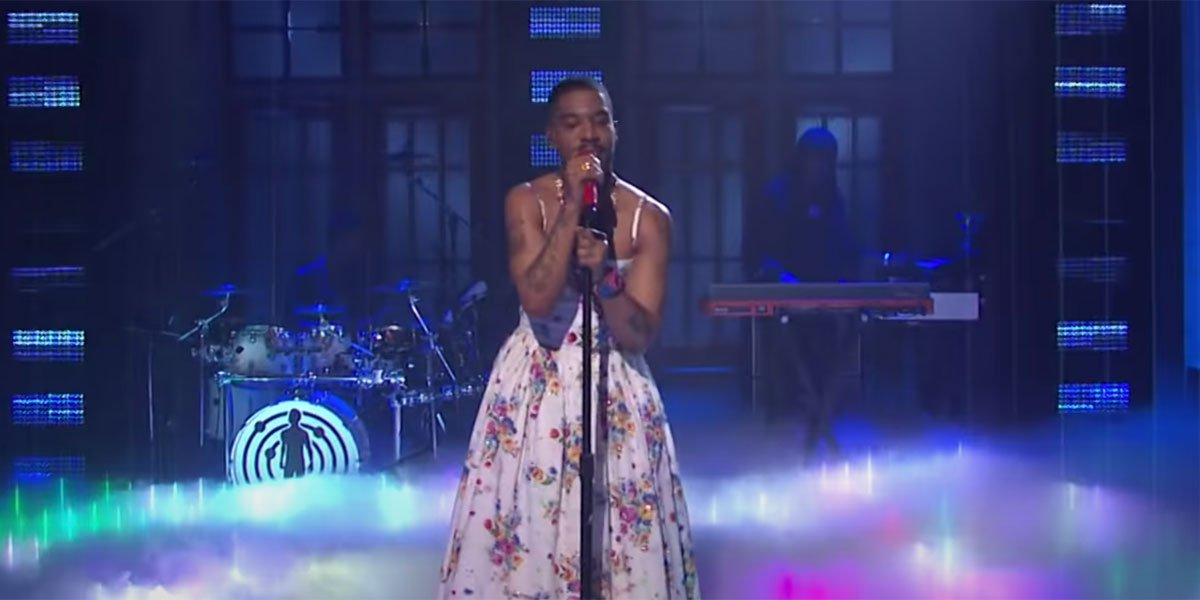 Kid Cudi wearing a white floral dress in a tribute to Kurt Cobain while singing into a microphone on SNL.