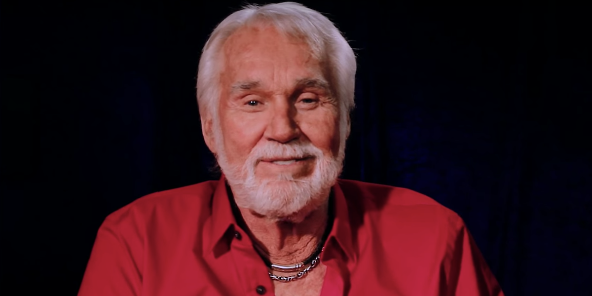 Kenny Rogers smiles and looks into the camera while giving a message to his fans in a 2015 video cal