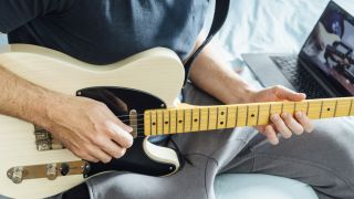 Man watches a guitar lesson video with his hands on the fretboard of his electric guitar