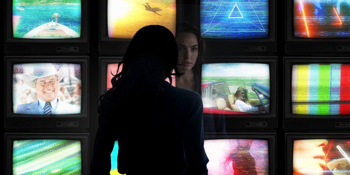 Gal Gadot as Wonder Woman looking at TV screens in Wonder Woman 1984