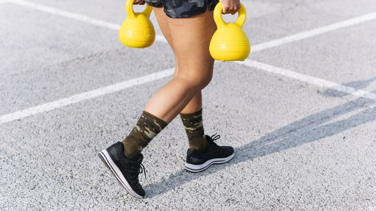 A woman wearing a pair of cross training shoes carries a pair of kettlebells