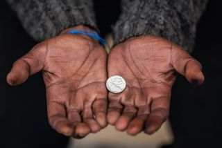 Hands holding a coin.
