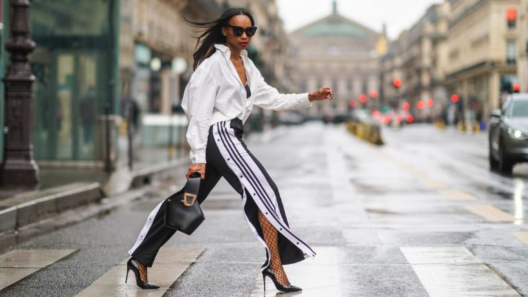 Emilie Joseph wears sunglasses, a white oversized long shirt from & Other Stories, black bras from Aubade, a Danse Lente black leather bag, black and white striped Adidas flared jogger sport pants