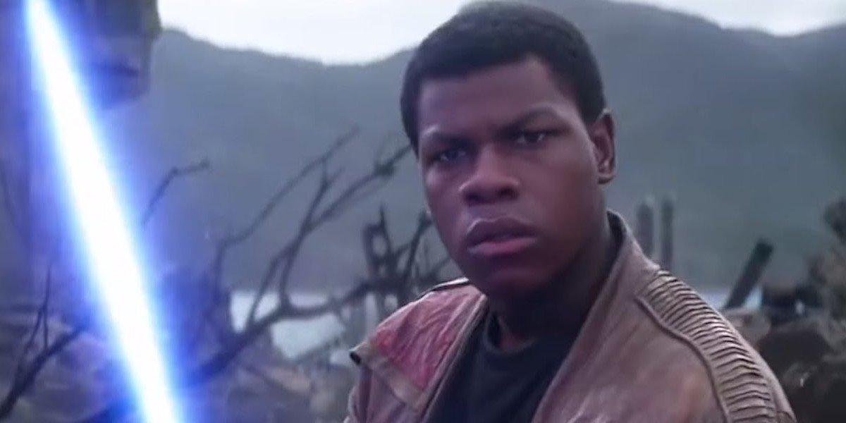 Finn (John Boyega) holds a lightsaber