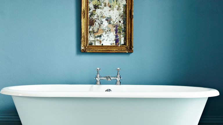 Free standing bathtub in blue painted bathroom