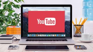 YouTube's logo is in a window on a MacBook on a desk that's very neatly arranged