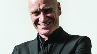 Wilko Johnson looking at the camera and smiling.