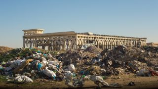 A garbage dump in front of a building ruined by war at Yasser Arafat International Airport in the Gaza Strip.