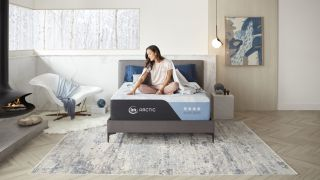 A woman with dark hair sits on the new Serta Arctic Mattress for cooler sleep